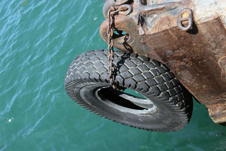 rubbery: big old black car tire hanging on a chain on the edge of pier as bumper for vessels
