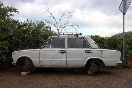 stary biały zardzewiały samochód bez kół jest w widoku z boku cegły