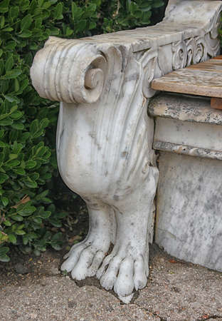sidewall: decorative white marble leg of stone garden bench in form of birds body with lion clawed paws in green park Stock Photo
