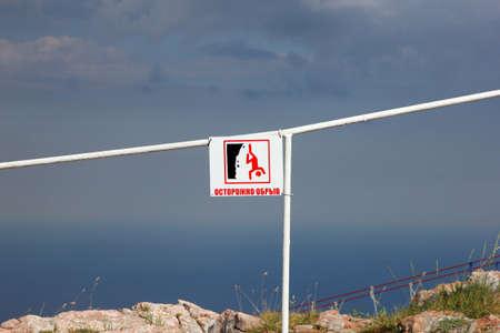 hombre cayendo: Muestra blanca cuadrada con precaución precipicio inscripción y la imagen del hombre que cae en la parte superior de la montaña