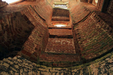 old photo: camera angle inside old ruined red brick bell tower Stock Photo