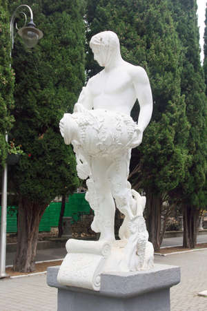 beautiful white plaster statue of Dionysus with pitcher in park