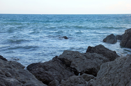 beautiful picturesque wild Black sea coast with big dark boulders and rocks in blue sea water