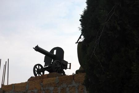 black silhouette of Maxim machinegun on brick pedestal