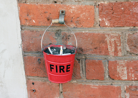 ashtray in the form of a small red fire bucket with the inscription FIRE on the brick wall of building
