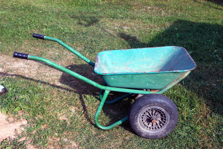 green color metal steel dirty old garden wheelbarrow side view with black inflatable wheel closeup