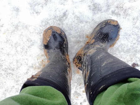 top view of feet in black dark dirty rubber boots or wellingtons in mud and clay on the snow ground Stock Photo