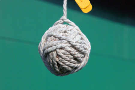ball tangle of white gray rope or uncut coil of lace closeup on green background 写真素材