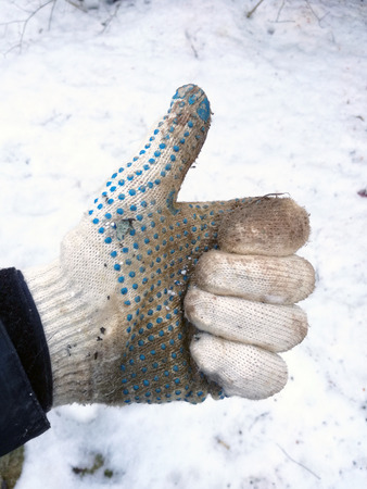 photo of hand in a dirty working white knitted cotton glove shows sign thumbs up on white snow background in winter closeup