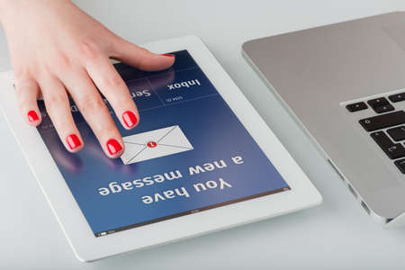 Woman s hand with red manicure opens a new email message on a tablet computer  photo