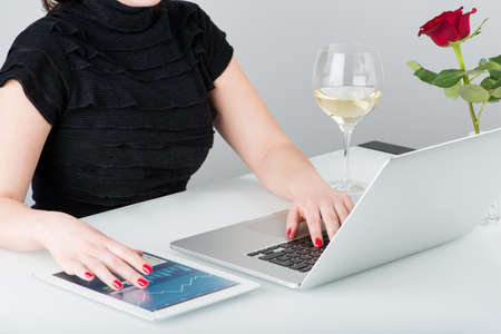 image consultant: A business woman is working with the modern laptop and tablet computer, Nearby on the table is a glass of wine and one rose  Stock Photo