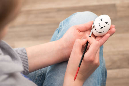The girl draws with a brush on an white egg, egg laughs  photo