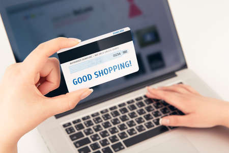 Woman s hand holding a bank card over a laptop On the card is written Good shopping You can put any inscription on the card