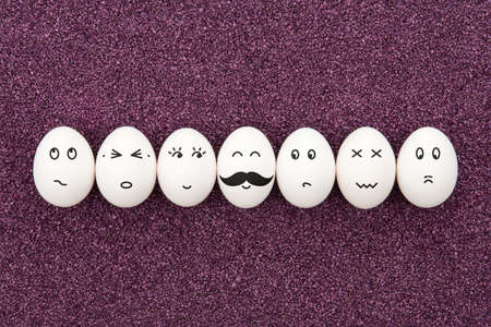 heed: Seven eggs with different facial expressions are lying on the decorative purple sand  Stock Photo