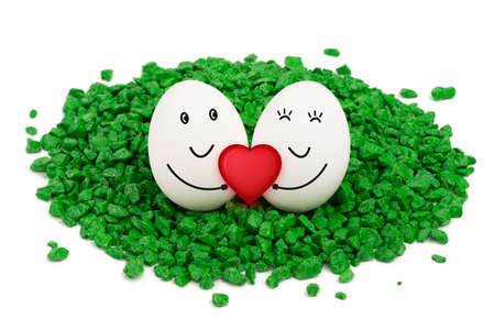 footsie: Two eggs lie on a green stones, are smiling and holding a red heart
