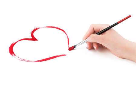 french manicure: Woman s hand draws a red heart shape with a brush on a white background