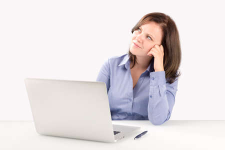 Business woman is sitting in front of a laptop leaning on one arm and looking into the top corner of the screen, business concept photo