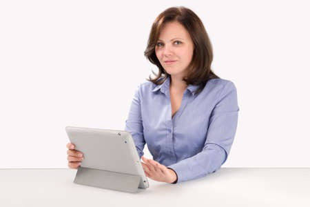 retina display: Business woman is working with tablet computer and looking at the camera, business concept Stock Photo