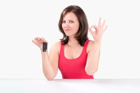 car keys: Happy young woman is holding car keys, showing ok gesture and looking at the camera