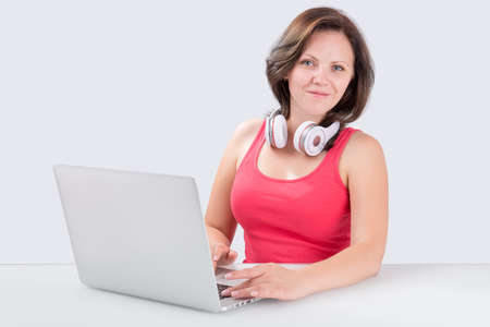 bluetooth: Young woman is sitting in front of laptop with bluetooth headphones on her neck and looking at the camera