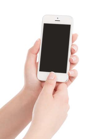 telefonos movil: Manos femeninas celebraci�n de blanco moderno tel�fono inteligente con pantalla en blanco y pulsar el bot�n con el pulgar. Aislado en el fondo blanco. Foto de archivo