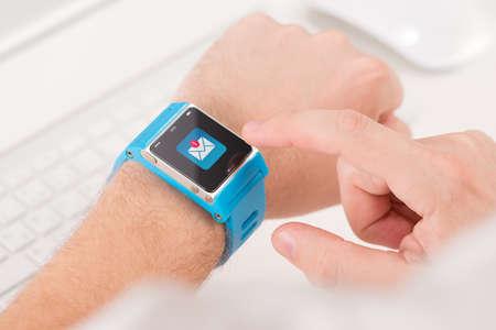 テクノロジー: 男性の指のスマートな時計に未読のメッセージのアイコンをタップします。