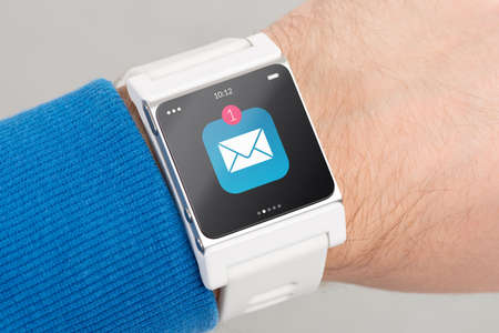 wristlet: Close up white smart watch with unread message icon on the screen is on hand