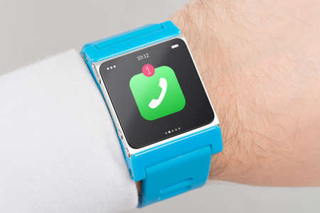 unanswered: Close up blue smart watch with missed phone call icon on the screen is on hand