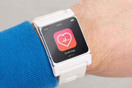 health icons: Close up white smart watch with health app icon on the screen is on hand