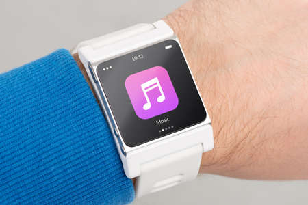 wearable: Close up white smart watch with music app icon on the screen is on hand