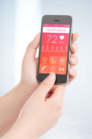 modern palmtop: Woman is scanning heartbeat cardiogram by modern smartphone with health book app on the screen. Stock Photo