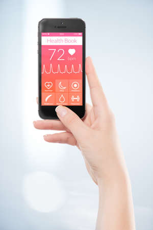 Woman hand is holding black mobile smart phone with health book app on the screen. Stock Photo