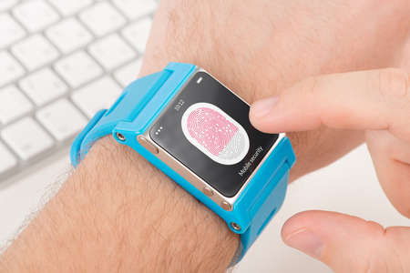 Man is scanning fingerprint for mobile security with blue smart watch. photo