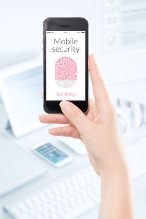 Woman hand is scanning fingerprint by modern black smartphone. Mobile security concept. photo