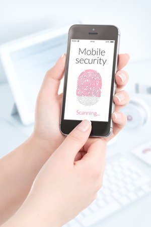Woman is scanning fingerprint by modern smartphone. Mobile security concept. photo