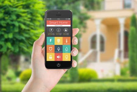 Mano femenina que sostiene negro teléfono móvil inteligente con la aplicación inteligente del hogar en la pantalla.