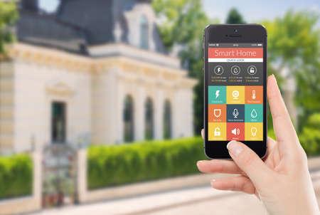 iluminacion: Mano femenina que sostiene negro teléfono móvil inteligente con la aplicación inteligente del hogar en la casa borrosa en el fondo de pantalla para el acceso a todos los mandos de tu casa y el cuidado de la seguridad en el hogar Foto de archivo