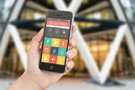 holding smart phone: Female hand holding black mobile smart phone with smart home application on the screen  Blurred house on the background  For access to all of the controls of your house and caring of home security  Stock Photo