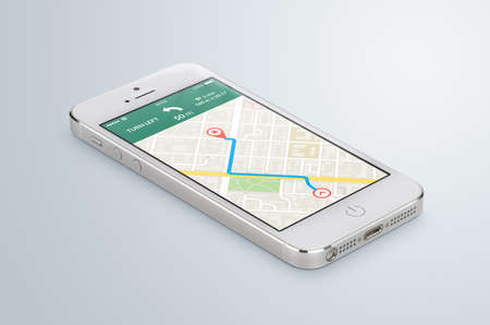 White modern smartphone with map gps navigation application with planned route on the screen lies on the gray surface. High quality. Stock Photo