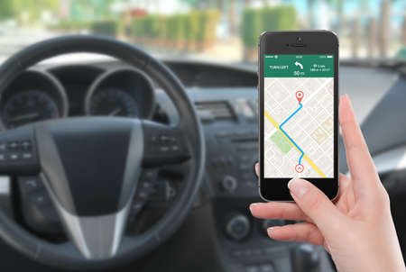 Female driver sitting in the car and holding black mobile smart phone with map gps navigation application with planned route on the screen. Blurred car interior on the background.