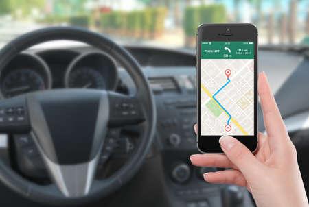 Vrouwelijke bestuurder in de auto zitten en die zwarte mobiele smart phone met kaart gps navigatie applicatie met geplande route op het scherm. Wazig auto-interieur op de achtergrond.