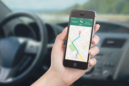 Vrouwelijke bestuurder in de auto zitten en die zwarte mobiele slimme telefoon met kaart gps navigatie-applicatie met geplande route op het scherm. Wazig auto-interieur op de achtergrond.