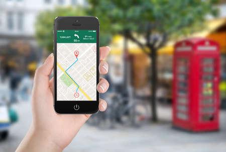 Mano femenina que sostiene negro teléfono móvil inteligente con aplicación de navegación GPS con mapa ruta planificada en la pantalla. Vista de la calle borrosa en el fondo.