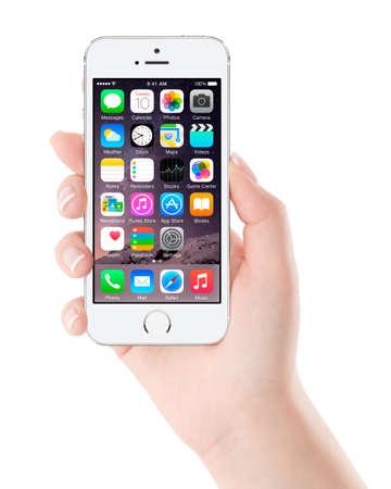 Varna, Bulgarije - 7 december 2013: Vrouwelijke hand die Apple Zilveren iPhone 5S weergeven van iOS 8 mobiele besturingssysteem, ontworpen door Apple Inc. geïsoleerd op een witte achtergrond. Redactioneel