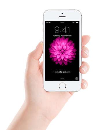 Varna, Bulgarije - 7 december 2013: Vrouwelijke hand die Apple Zilveren iPhone 5S met slot scherm op het scherm, ontworpen door Apple Inc. geïsoleerd op een witte achtergrond. Redactioneel