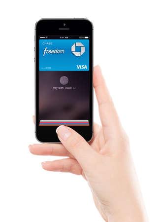 Varna, Bulgarije - 7 december 2013: Vrouwelijke hand die Apple Space Gray iPhone 5S met touch id Apple Pay-technologie, ontworpen door Apple Inc. geïsoleerd op een witte achtergrond.