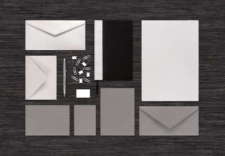 Top view of branding identity mock-up with templates for design presentation or portfolio on black table. Consists of envelopes, paper, notebook, pen, eraser, clips, business card. photo
