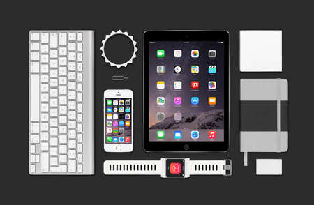 Varna, Bulgaria - February 09, 2015: Top view of Apple products mockup. Consists of ipad air 2, iphone 5s, keyboard, smartwatch concept, notebook, eraser, bracelet, reminder.
