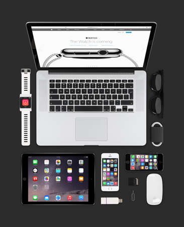 5s: Varna, Bulgaria - February 09, 2015: Top view of Apple gadgets technology mockup consisting macbook pro with apple watch web page on the screen, ipad air 2, smart watch concept, iphone 5s, magic mouse.