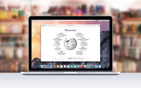 Varna Bulgaria  November 03 2013: Directly front view of Apple 15 inch MacBook Pro Retina with an open tab in Safari which shows Wikipedia web page. Blurred library on the .